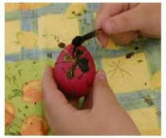 Pysanky: this egg has been dyed in various colours, most recently red.  Areas being covered in wax at this stage will remain red